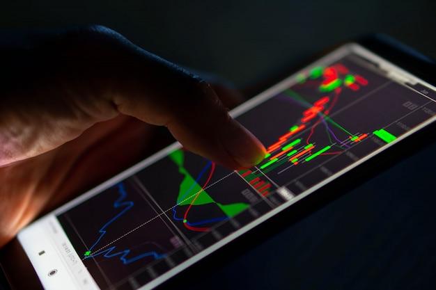 Hombre toque gráfico de velas del mercado de valores en el teléfono inteligente