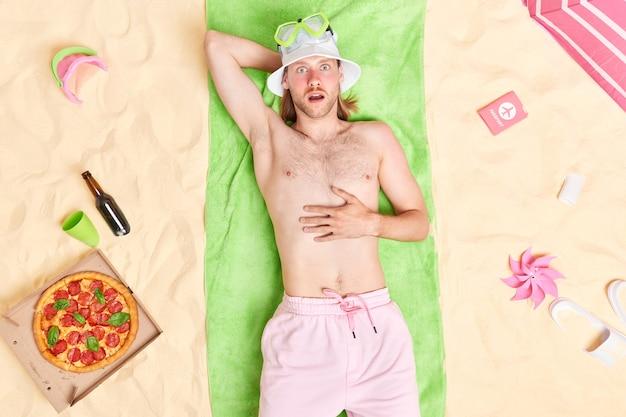 Hombre con torso desnudo cara roja quemada por el sol yace sobre una toalla verde pasa las vacaciones de verano en la playa come pizza bebe cerveza posa en la playa de arena ropa de playa y pantalones cortos