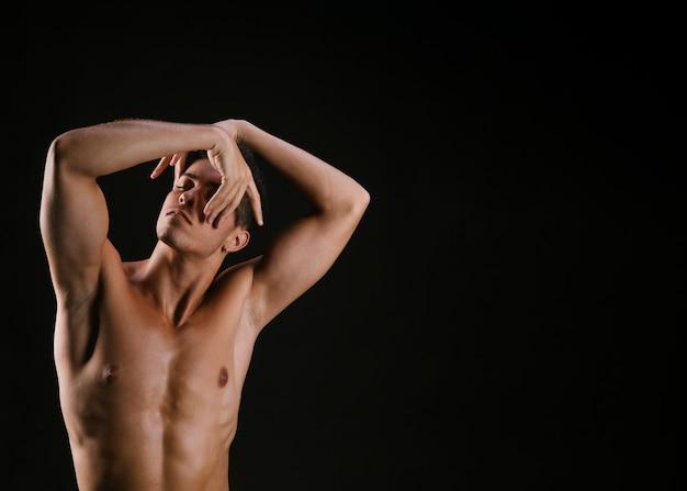 Hombre con torso desnudo doblando la mano ante la cara