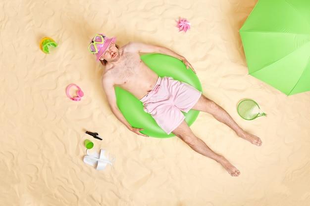 El hombre con el torso desnudo se encuentra en un traje de baño verde inflado rodeado de accesorios de playa posa en la arena blanca tiene una expresión de enojo y toma el sol solo