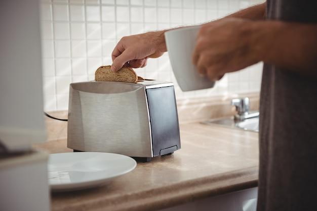 Hombre tostando pan para el desayuno y tomando café