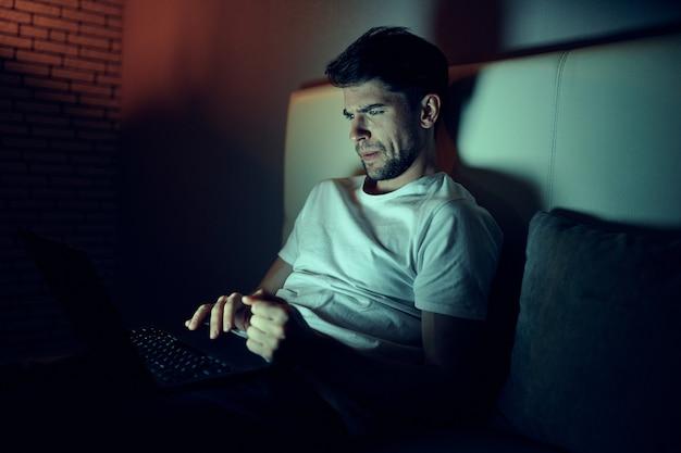 Un hombre trabaja en una computadora portátil en la cama, una mujer amada duerme, trabajo nocturno, traición