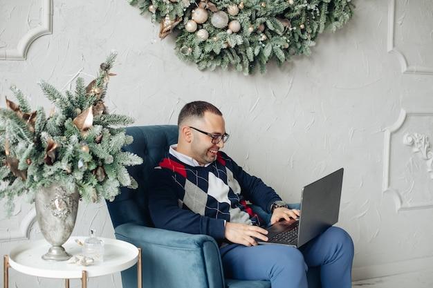 Un hombre trabaja con una computadora portátil en casa en nochebuena