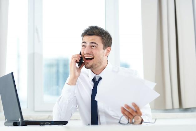 Un hombre trabaja en una computadora portátil, un hombre en una oficina