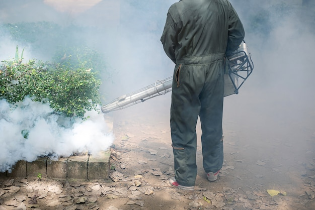 El hombre trabaja empañándose para eliminar el mosquito y prevenir la propagación del dengue
