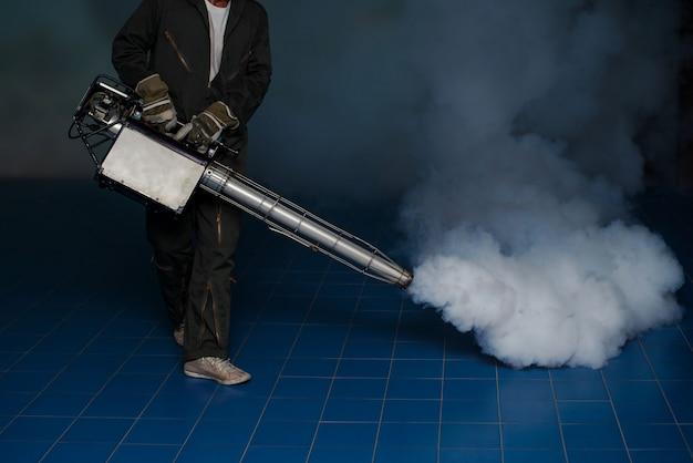 El hombre trabaja empañándose para eliminar el mosquito para prevenir la propagación de la fiebre del dengue en la comunidad