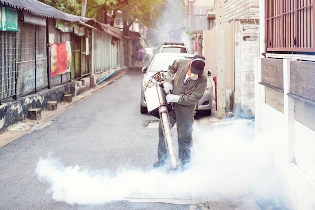 El hombre trabaja empañándose para eliminar el mosquito para prevenir la propagación de la fiebre del dengue y el virus zika