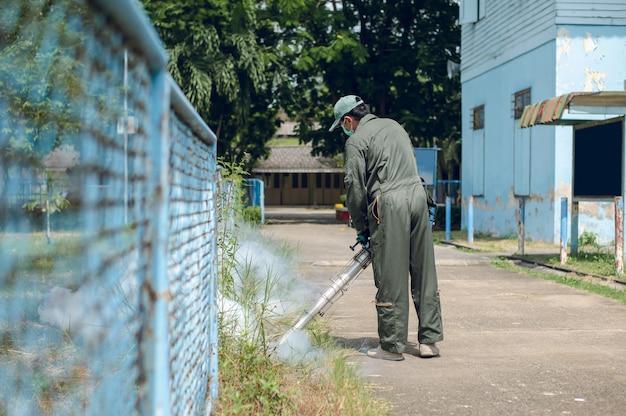 El hombre trabaja empañándose para eliminar el mosquito para prevenir la propagación de la fiebre del dengue