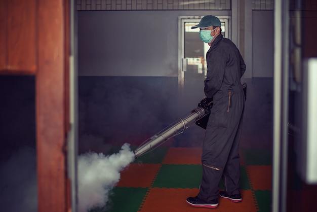 El hombre trabaja empañándose para eliminar el mosquito