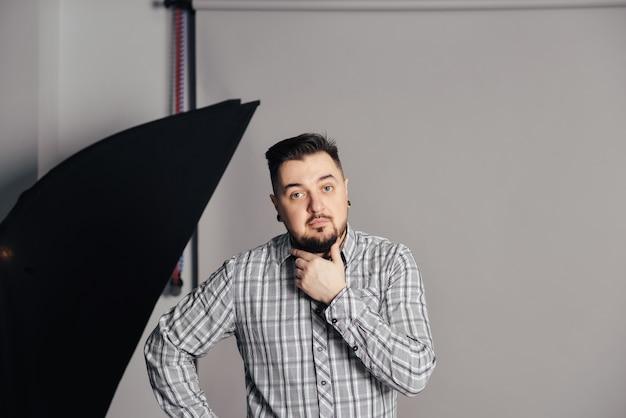 El hombre trabaja en un estudio fotográfico con luz, un asistente de director, un proceso creativo de sesión de fotos de caja