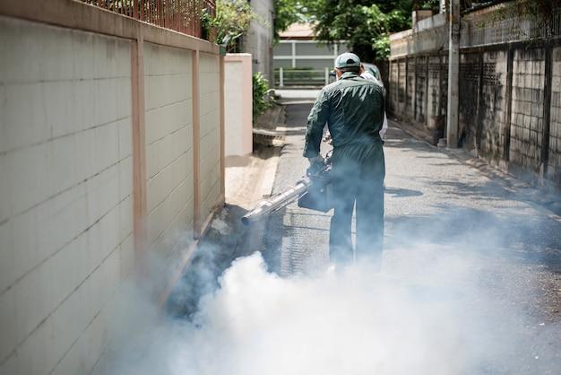 El hombre trabaja con nebulización, deshacerse de los mosquitos para detener la propagación de la fiebre del dengue