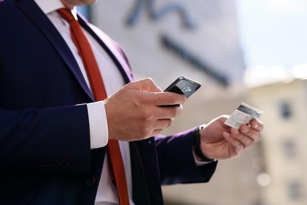 El hombre trabaja con tarjeta de crédito y teléfono.