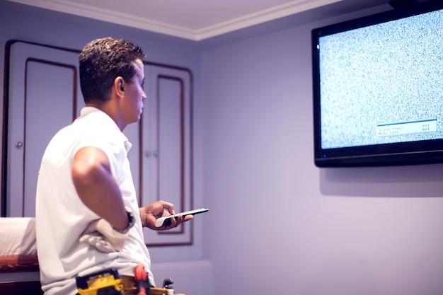 Un hombre trabajador arregla tv con pantalla azul