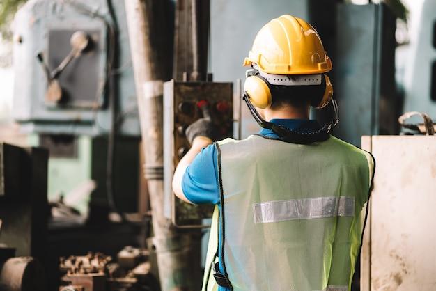 Hombre trabajador asiático que trabaja en ropa de trabajo de seguridad con casco amarillo.