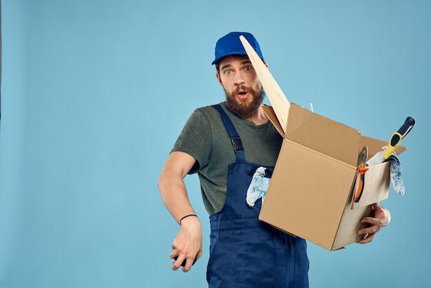 Hombre trabajador en caja uniforme herramientas construcción fondo azul. foto de alta calidad
