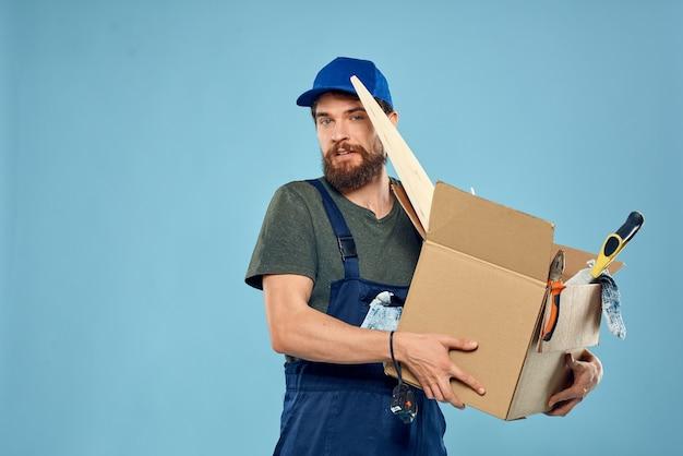 Hombre trabajador en caja uniforme herramientas construcción fondo azul.