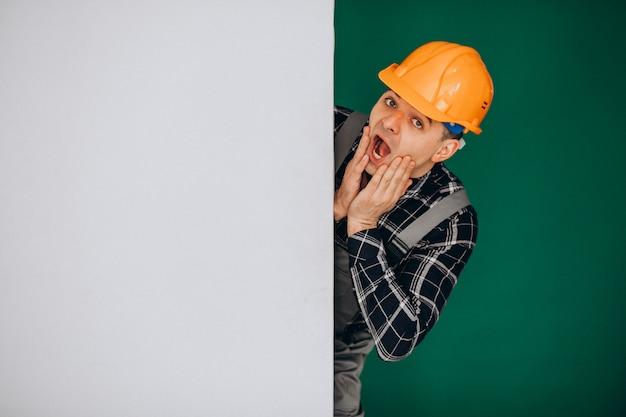 Hombre trabajador en casco aislado en pared verde