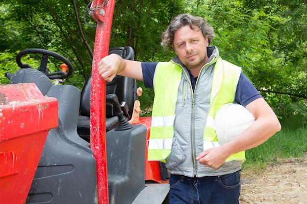 Hombre trabajador de la construcción con minicargadora