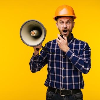 Hombre trabajador enojado en casco naranja con un megáfono sobre fondo amarillo - imagen