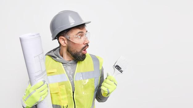 El hombre trabajador industrial posa con planos y pincel de pintura lleva casco, gafas protectoras, uniforme