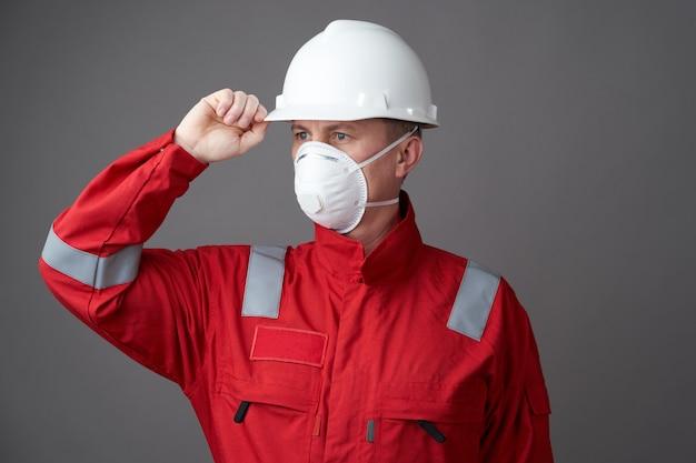 Hombre trabajador con máscara higiénica, casco general y protector