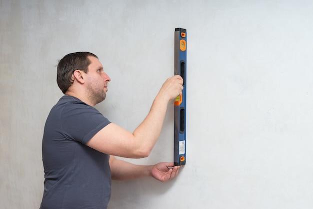 Hombre trabajador de paneles de yeso o yesero control de nivel