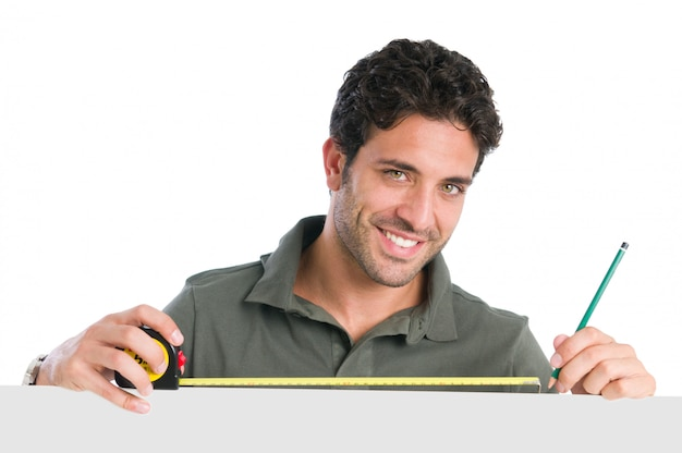 Hombre trabajador sonriente midiendo con cinta encima de un cartel en blanco listo para su texto