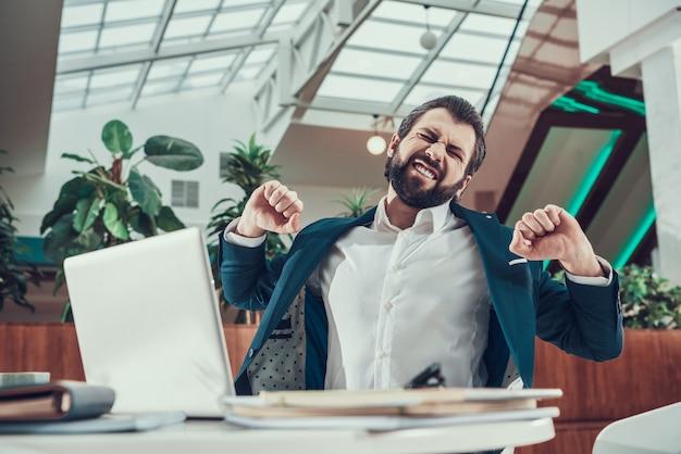 Hombre trabajador en traje ejercicio estirando los brazos en la oficina.