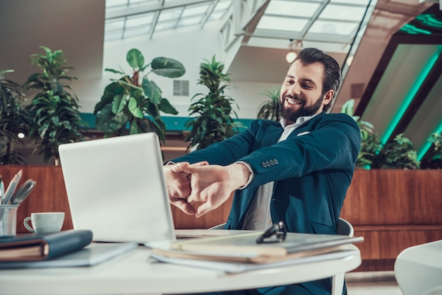 Hombre del trabajador en el traje que ejercita estirando los brazos en oficina.