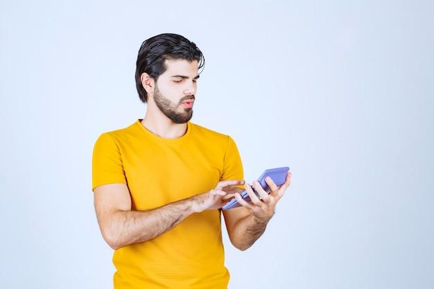 Hombre trabajando con calculadora y pensando.