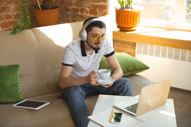 Hombre trabajando desde casa durante el coronavirus o la cuarentena covid-19, concepto de oficina remota