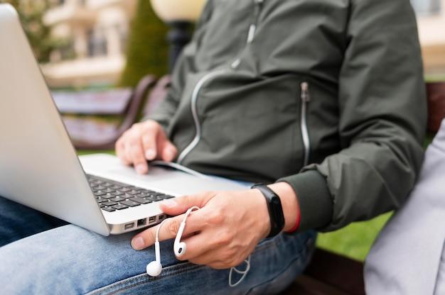 Hombre trabajando en la computadora portátil afuera con auriculares