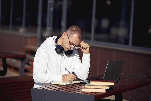 Hombre trabajando en una computadora portátil y escribiendo en un cuaderno sentado en la calle en una mesa