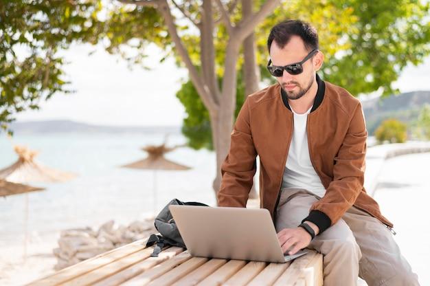 Hombre trabajando en la computadora portátil mientras está en la playa