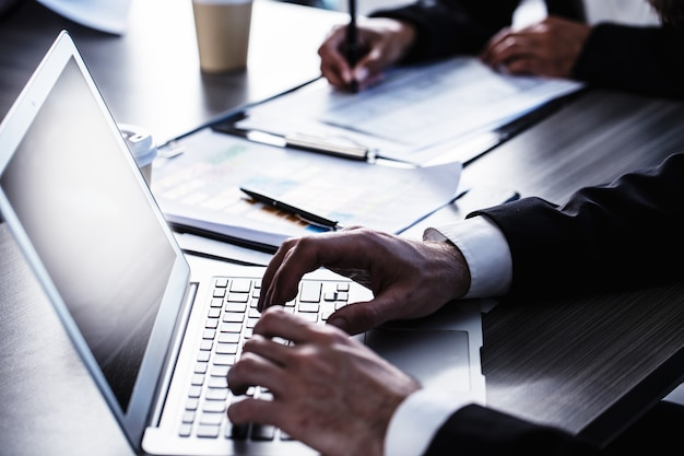Hombre trabajando en una computadora portátil en la oficina. concepto de interconexión y uso compartido de internet