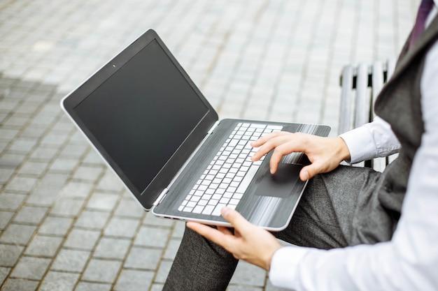 Hombre trabajando en la computadora portátil en el parque en un día soleado