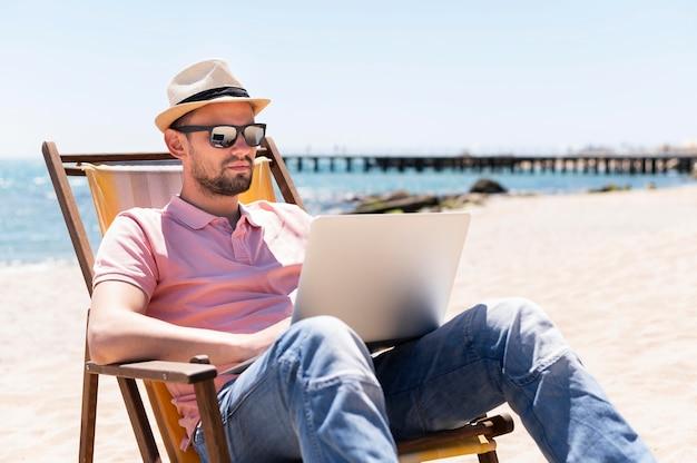 Hombre trabajando en la computadora portátil en la silla de playa