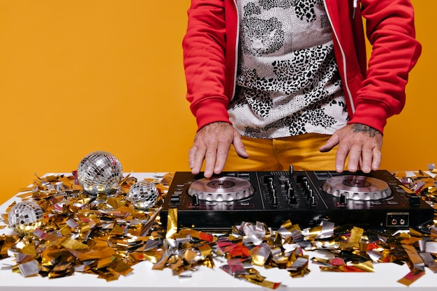 Hombre trabajando con controlador de dj en pared naranja