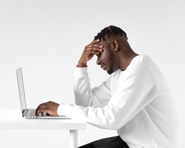 Hombre trabajando en el escritorio de tiro medio