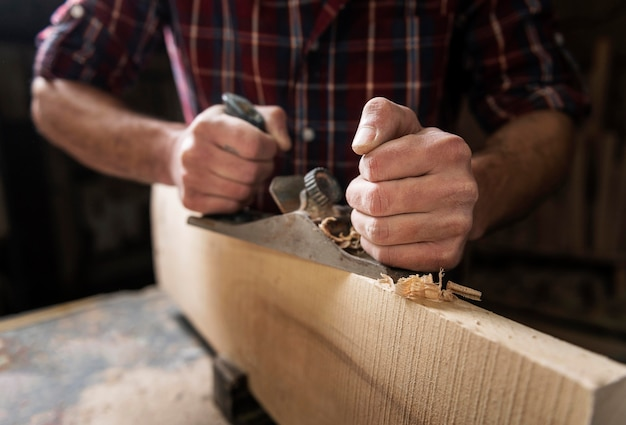 Hombre trabajando con madera en el taller Foto gratis