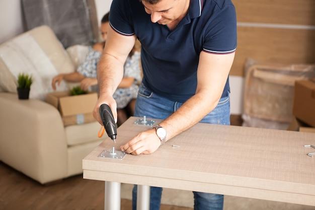 El hombre está trabajando con el montaje de muebles con un destornillador eléctrico en la nueva casa.