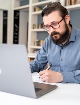 Hombre trabajando con ordenador portátil de cerca
