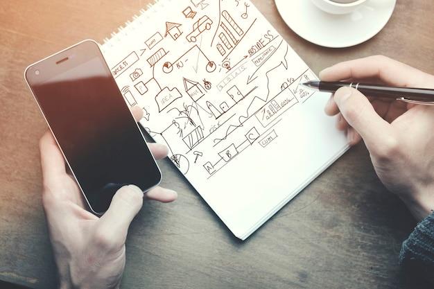Hombre trabajando -pluma de mano y teléfono, taza de café en la mesa de madera