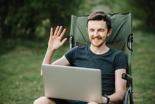 Hombre trabajando en un portátil en la naturaleza