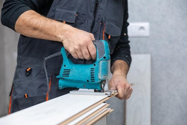 Hombre trabajando con sierra de calar en madera laminada blanca