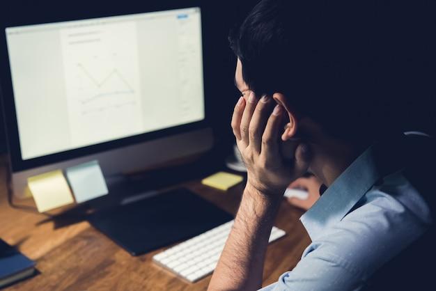 Hombre trabajando en su pc de escritorio en la noche haciendo horas extras