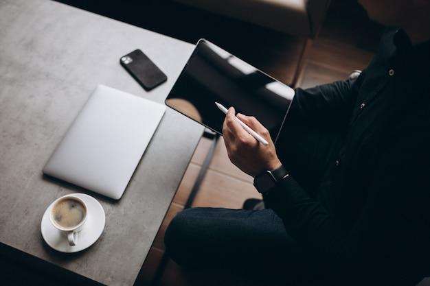 Hombre trabajando en tableta de cerca en la mesa