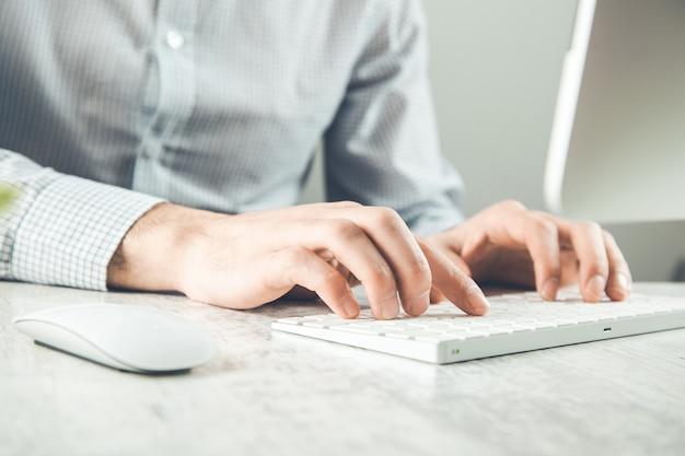 Hombre trabajando en el teclado de la computadora en el escritorio
