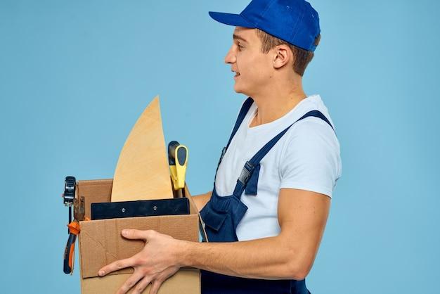 Hombre de trabajo en caja uniforme con entrega de cargador de herramientas azul