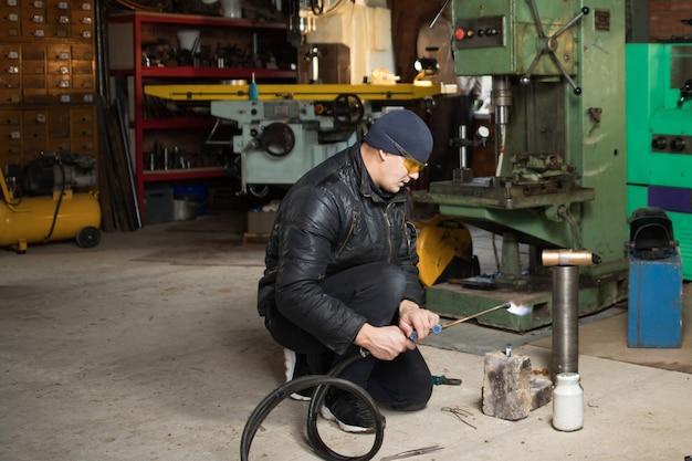 El hombre de trabajo es un soldador con máscara, producto de metal en el garaje de su casa, con soldadura de gas ardiente con llama